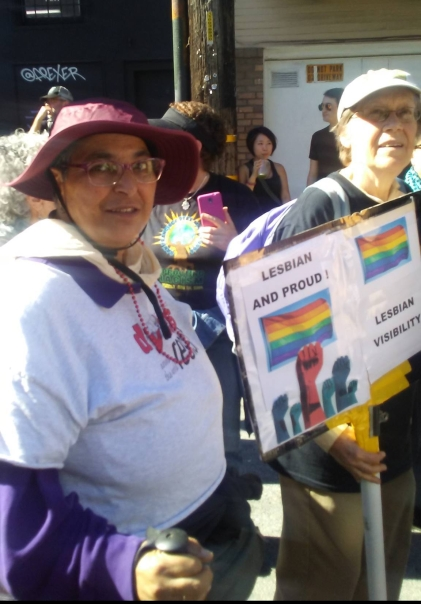"""Two Amazons march in San Francisco with a sign that shows raised fists under two rainbow flags. The sign reads, """"LESBIAN AND PROUD!"""" and """"LESBIAN VISIBILITY"""""""