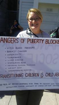 """One Amazon's sign reads, """"Dangers of puberty blockers: high blood pressure, breast cancer, infertility, thrombisis, liver disease, dysfiguring acne, abnormal glucose tolerance, weight gain, cardiovascular disease. Transitioning children IS child abuse! ~80-95% of gender dysphoric kids come to identify with their biological sex, oftentimes finding happiness as lesbian and gay individuals."""" On the back it reads, """"Change Our Society Not Your Body."""""""