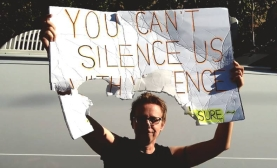 "One Amazon holds her torn sign high. It reads, ""You Can't Silence Us With Violence - Resist Lesbian Erasure."""