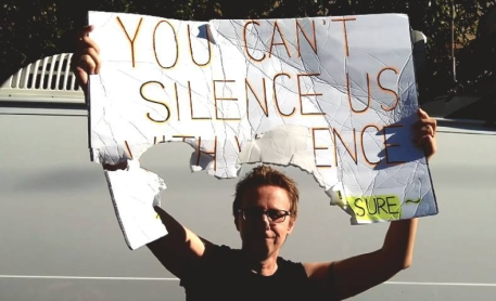 """One Amazon holds her torn sign high. It reads, """"You Can't Silence Us With Violence - Resist Lesbian Erasure."""""""