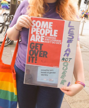"One woman carries a sign in Belfast that reads, ""Some people are Lesbians and Lesbians don't do dick. Get over it! Lesbian Not Queer. Sexuality isn't based on gender identity. You guys just hate Lesbians."