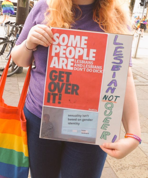 """One woman carries a sign in Belfast that reads, """"Some people are Lesbians and Lesbians don't do dick. Get over it! Lesbian Not Queer. Sexuality isn't based on gender identity. You guys just hate Lesbians."""