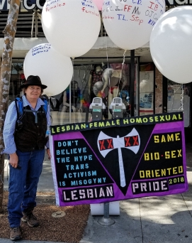 """LA Lesbian activist Gaye Chapman stands by her sign that shows several slogans: """"LESBIAN - FEMALE - HOMOSEXUAL""""; """"Don't believe the hype, transactivism is misogyny""""; """"Same bio-sex oriented""""; """"LESBIAN PRIDE 2018"""". A giant labrys with """"XX"""" on either blade is front and center."""