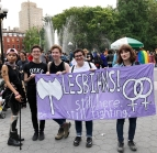 "Dykes in New York City hold a lavender banner that reads, ""LESBAINS! Still here, Still fighting"" flanked by a giant labrys and two interlocked female symbols."