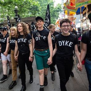 """Women wearing black shirts with """"DYKE"""" in white letters march through NYC streets hand-in-hand."""
