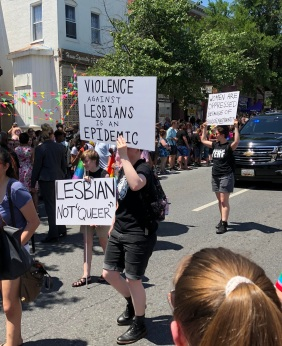 "Three Lesbians march on the street holding signs that read, ""Violence against lesbians is an epidemic,"" ""Lesbian Not Queer,"" and ""Women are oppressed because of biology not identity."""