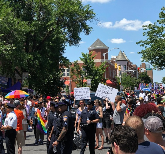 """People gather at Baltimore Pride. Two signs that read, """"Women are oppressed because of biology not identity"""" and """"Violence against Lesbians is an epidemic"""" stand out in the crowd."""