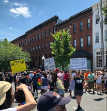 """Members of the crowd watch three Lesbians march on the street carrying signs that read, """"Woman is not a feeling,"""" """"Change our society not your body,"""" and """"Women are oppressed because of biology not identity."""" One woman snaps a photo of the marchers."""