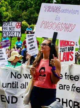 """One brave feminist in Queensland holds a sign that reads, """"Don't Believe the Hype, Transactivism Is Misogyny."""" Behind her men carry signs that read, """"Trans Women are Women."""""""