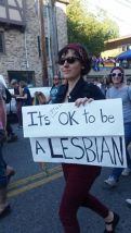 "A fearless dyke marches at Seattle Pride with a sign that reads, ""It's STILL OK to be a Lesbian."""