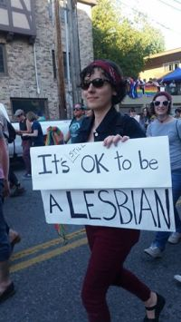 """A fearless dyke marches at Seattle Pride with a sign that reads, """"It's STILL OK to be a Lesbian."""""""