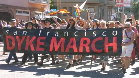 """Dykes march together, bellowing behind a black banner that reads, """"San Francisco"""" in white and """"DYKE MARCH"""" in red."""