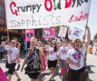 """The Grumpy Old Dykes, Sapphists, and Lesbians lead the march holding their banners high and wearing white t-shirts with pink uterus shields that read """"LESBIAN"""". One reads sign in the background reads, """"Lavender Menace, My Lesbian Heroes."""""""